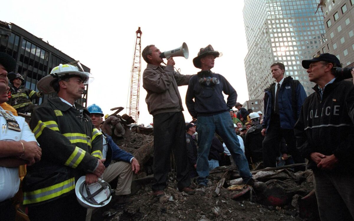 Standing atop rubble with retired New York City firefighter Bob Beckwith, President George W Bush rallies firefighters and rescue workers during an impromptu speech at the site of the collapsed World Trade Center.