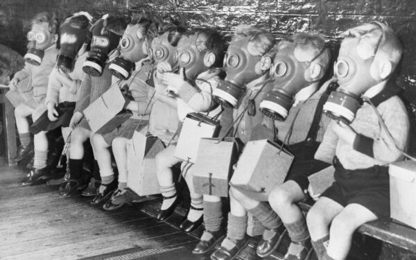 Row of children sit down with gas masks on. A warning from history.