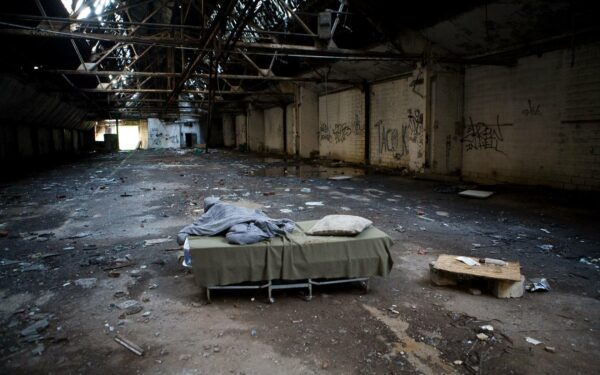 Homeless person finds shelter in disused warehouse.