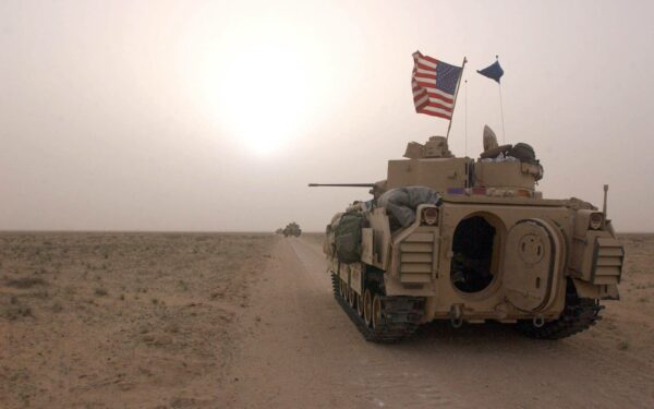 US Army tank drives along a road in Iraq