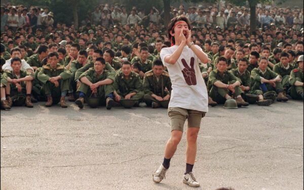 Student stands in front of group of sitting soldiers.