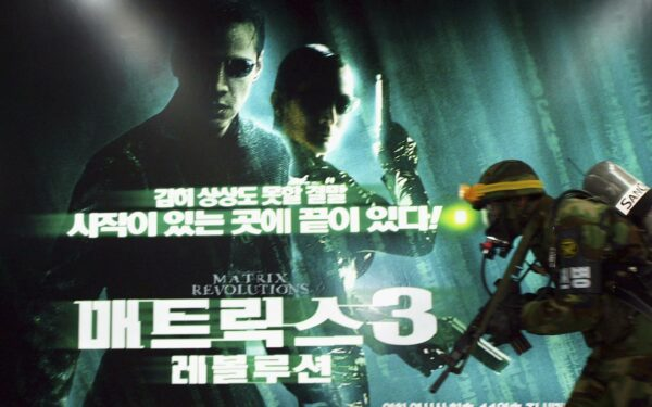 A South Korean soldier runs past a billboard poster for 'Matrix Revolutions' during an anti-chemical weapon attack drill at a subway station in 2003 in South Korea.