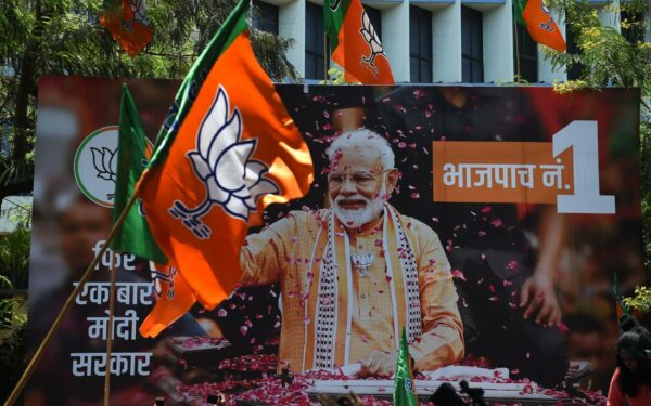 A billboard with an image of Indian Prime Minister Narendra Modi is surrounded by Bharatiya Janata Party (BJP) flags as supporters gather to celebrate election results outside the BJP headquarters in Mumbai in 2019.