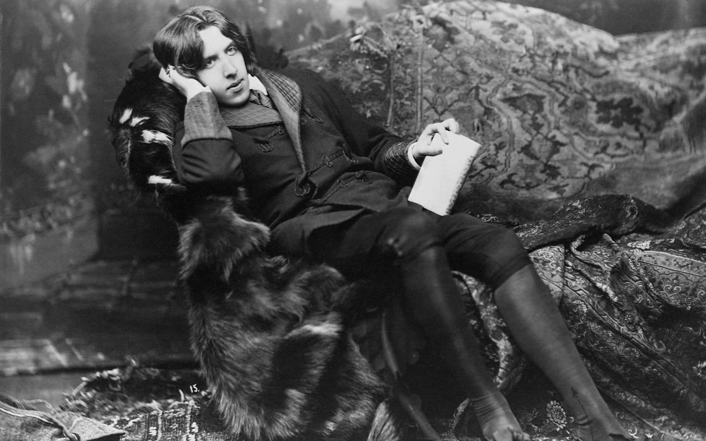 Poet and novelist, Oscar Wilde, (1854-1900), in his typical costume of a velvet robe and black silk stockings. Wilde was one of the leading dandies of the Victorian era. Credit: CORBIS/Corbis via Getty Images