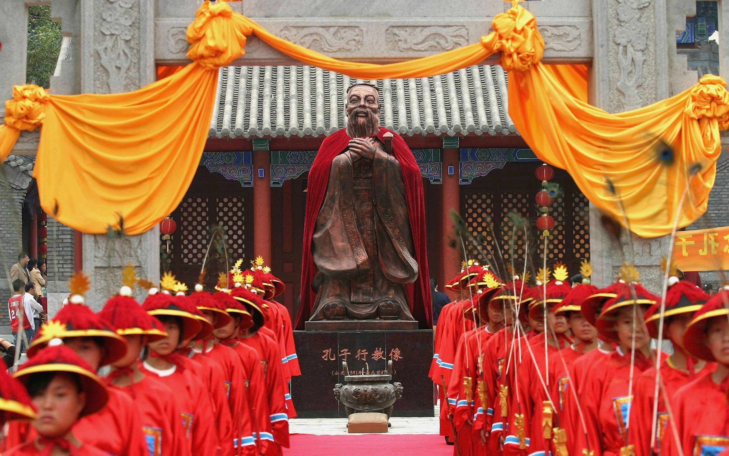 Students dressed in ancient clothes stand in front of the statue of Confucius (551-479 BC), during a ceremony to worship the Chinese philosopher and educator at the Changchun Confucian Temple on September 25, 2005 in Changchun of Jilin Province, China. Credit: China Photos/Getty Images