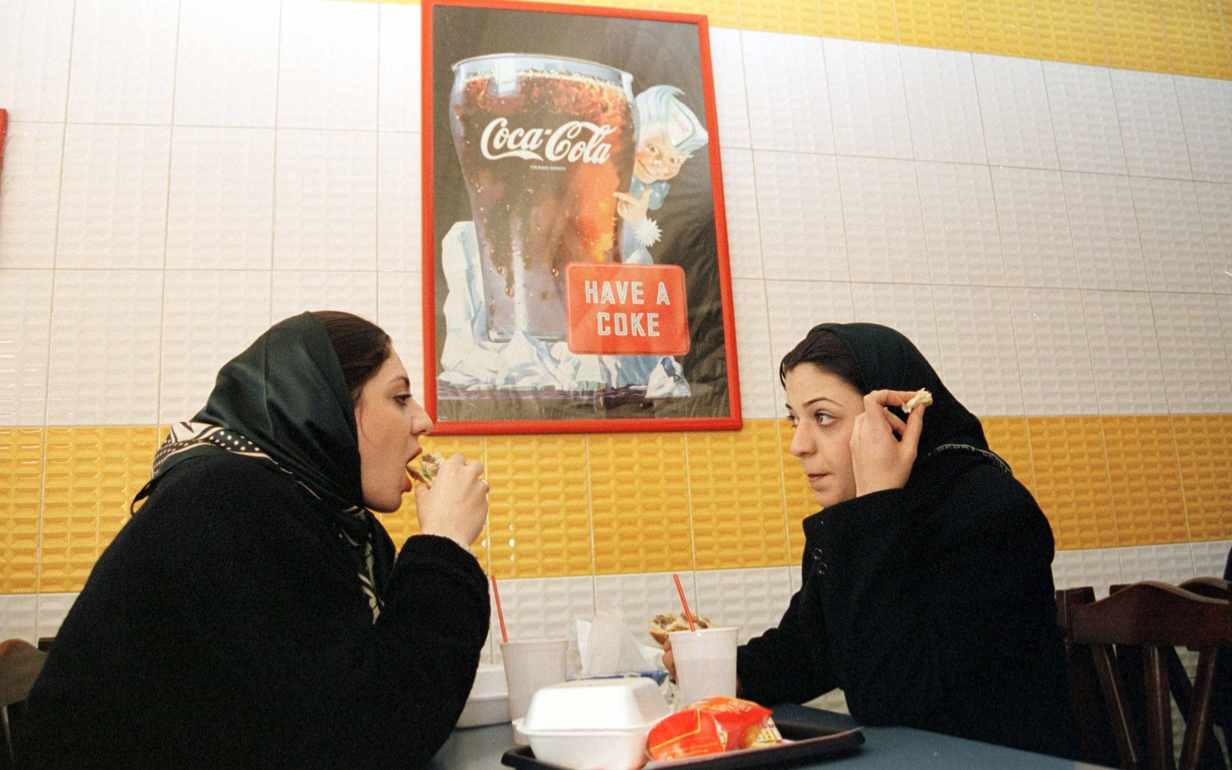 Two young women in veils enjoy a hamburger whilst sitting in front of a Coca Cola poster in a Star Burger fast food restaurant in northern Tehran, June 2001. Credit: Kaveh Kazemi/Getty Images