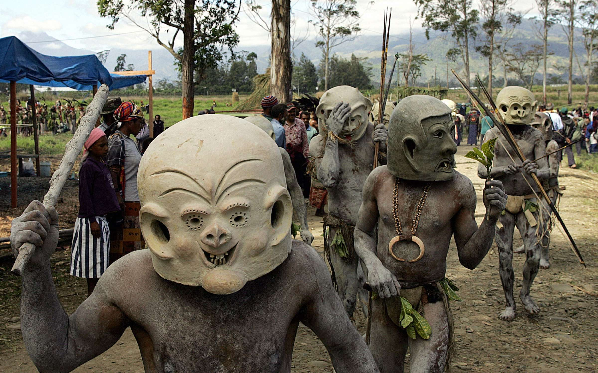 Asaro mud men from Goroka walk to the annual sing-sing cultural festival in Mount Hagen in 2004. Over 70 tribes put aside their ethnic tensions to come together once a year in the remote frontier town to celebrate the cultural diversity of Papua New Guinea. Credit: TORSTEN BLACKWOOD/AFP via Getty Images