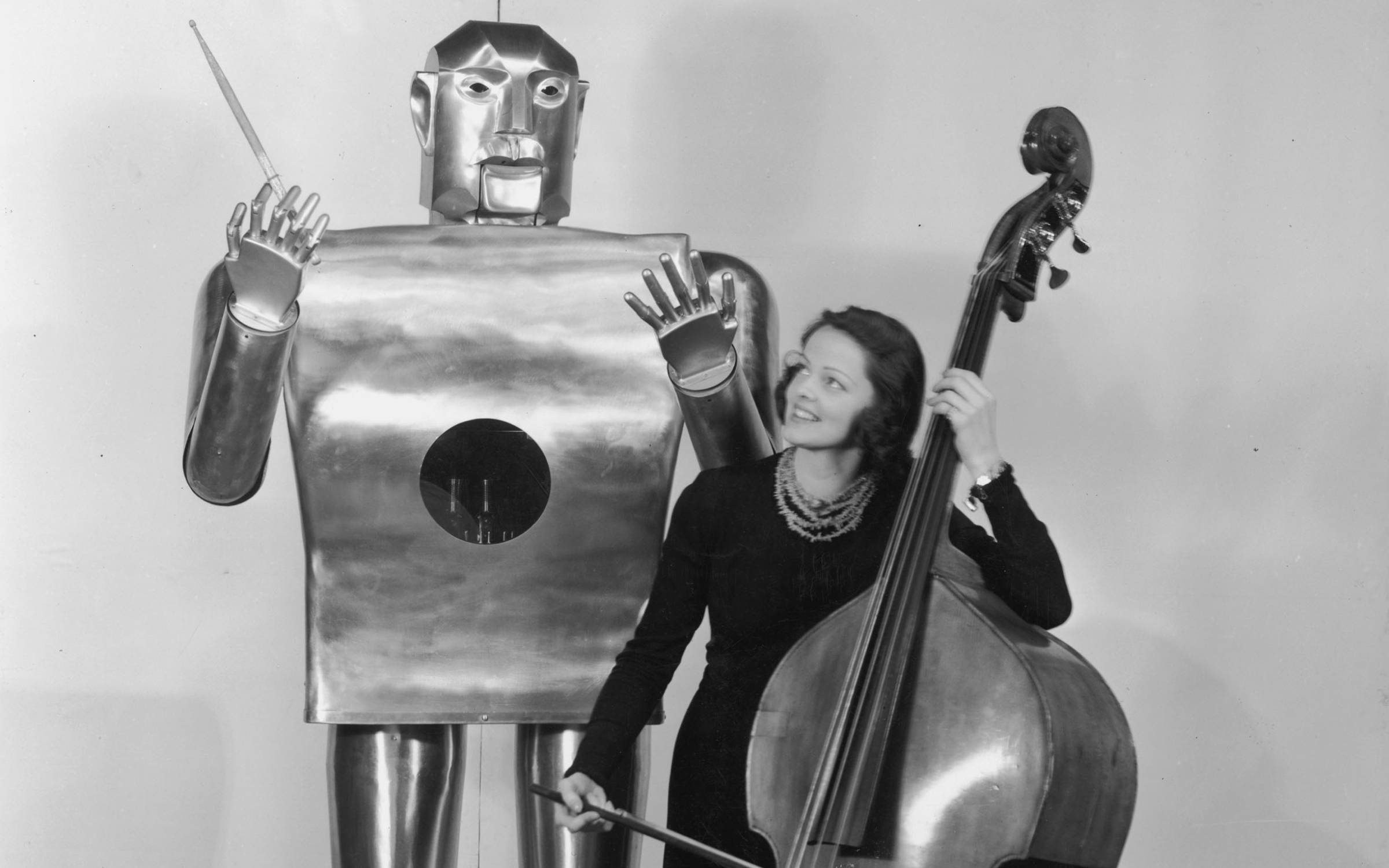 Musician Lois Kendall plays the cello while a mechanical man named Elektro 'conducts' on stage as part of a Westinghouse Electric and Manufacturing Co demonstration at the World's Fair, New York City, 1939. Credit: Hulton Archive/Getty Images