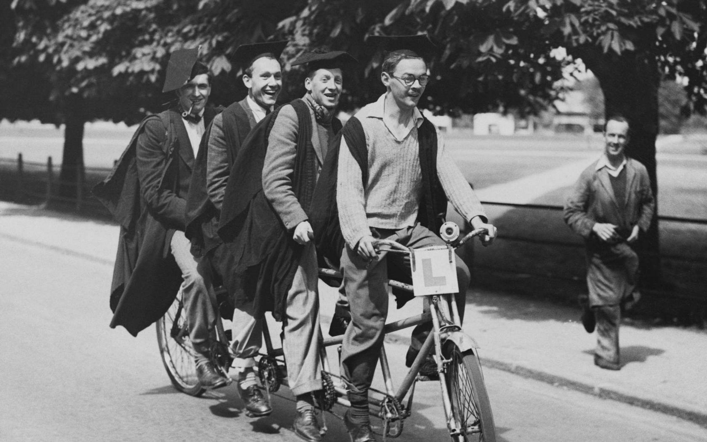 Four Cambridge students ride a four seat tandem bike on campus.