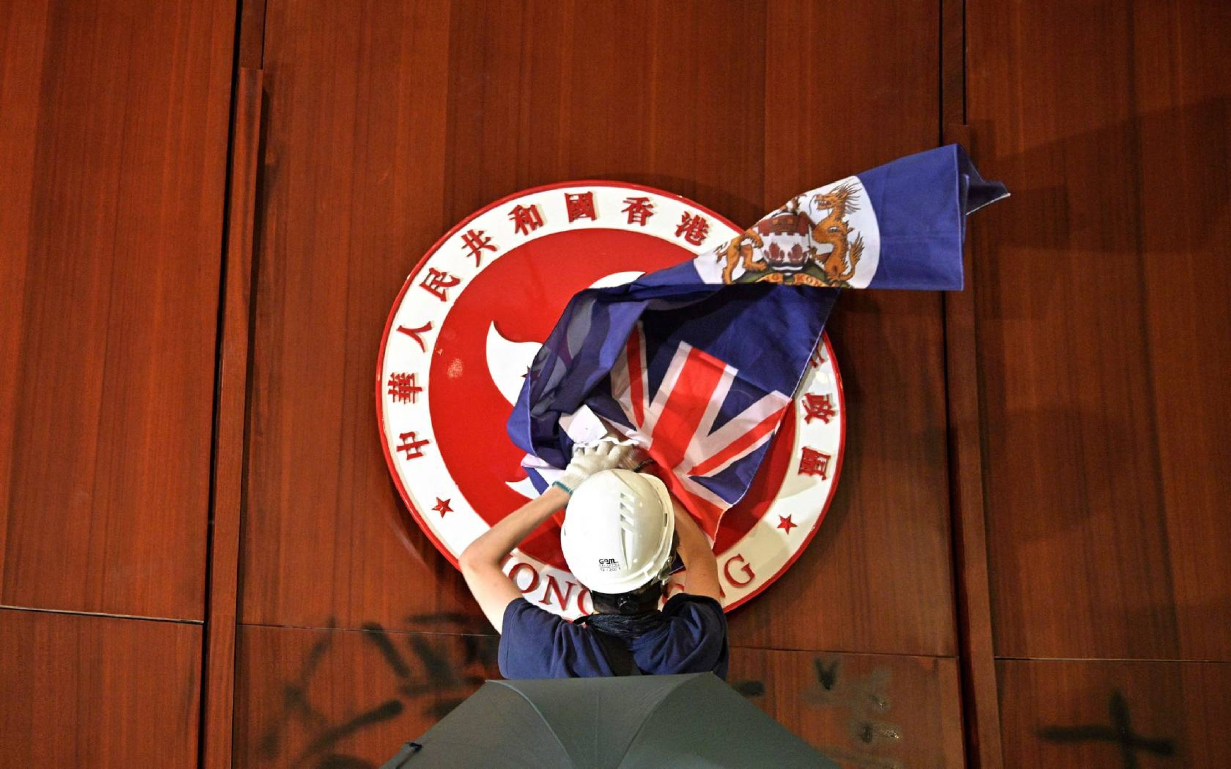 A protester attempts to cover the Hong Kong emblem with a British colonial flag after they broke into the government headquarters in Hong Kong in June 2019, the 22nd anniversary of the city's handover from Britain to China.