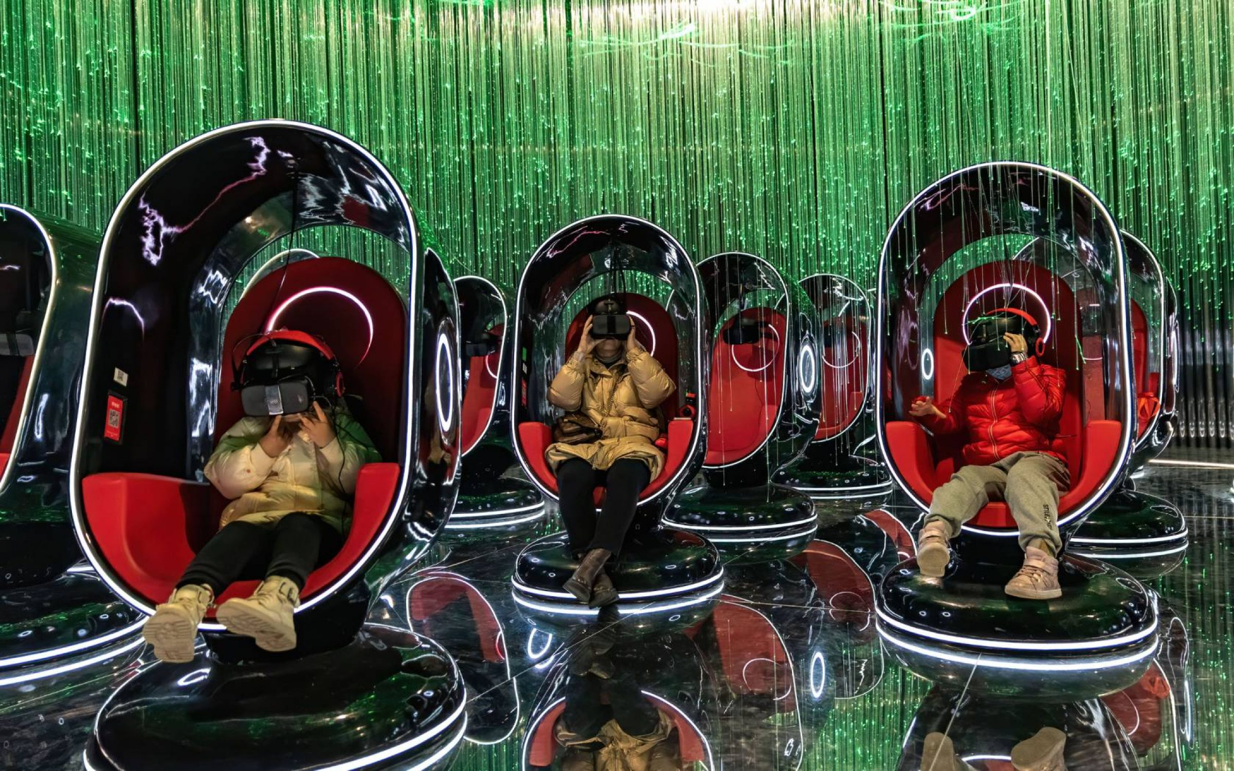 People wearing VR headsets watch films during an exhibition at 'AHSPACE' immersive live broadcast base in Hefei, Anhui Province of China.
