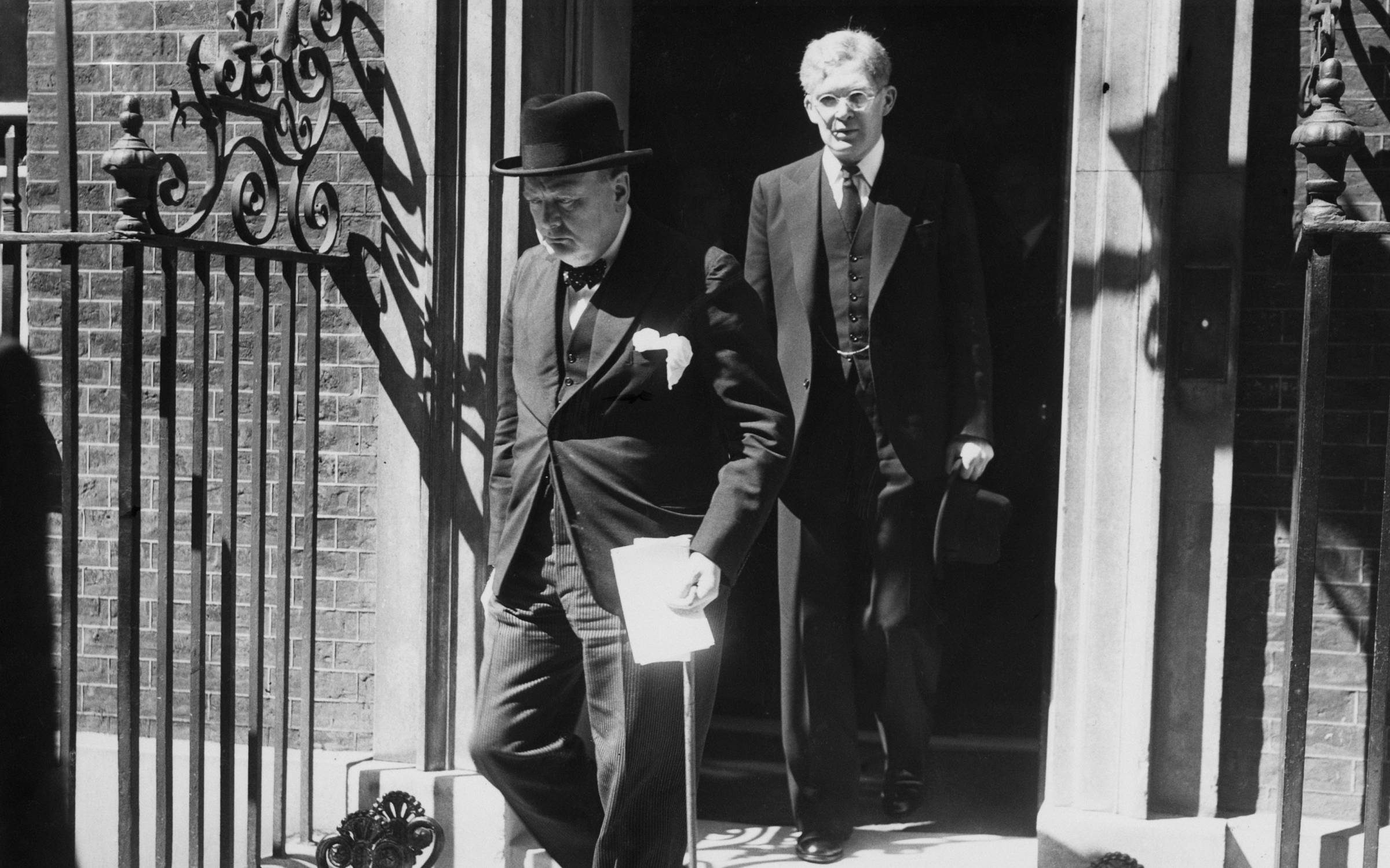 London, England, 18th June, 1940, British Prime Minister Winston Churchill (1874-1965) leaves Number 10 Downing Street to make his statement in the House of Commons on the capitulation of France during World War Two. Behind him is Parliamentary Private Secretary Brendan Bracken (1901-1958). (Photo by Popperfoto via Getty Images/Getty Images)