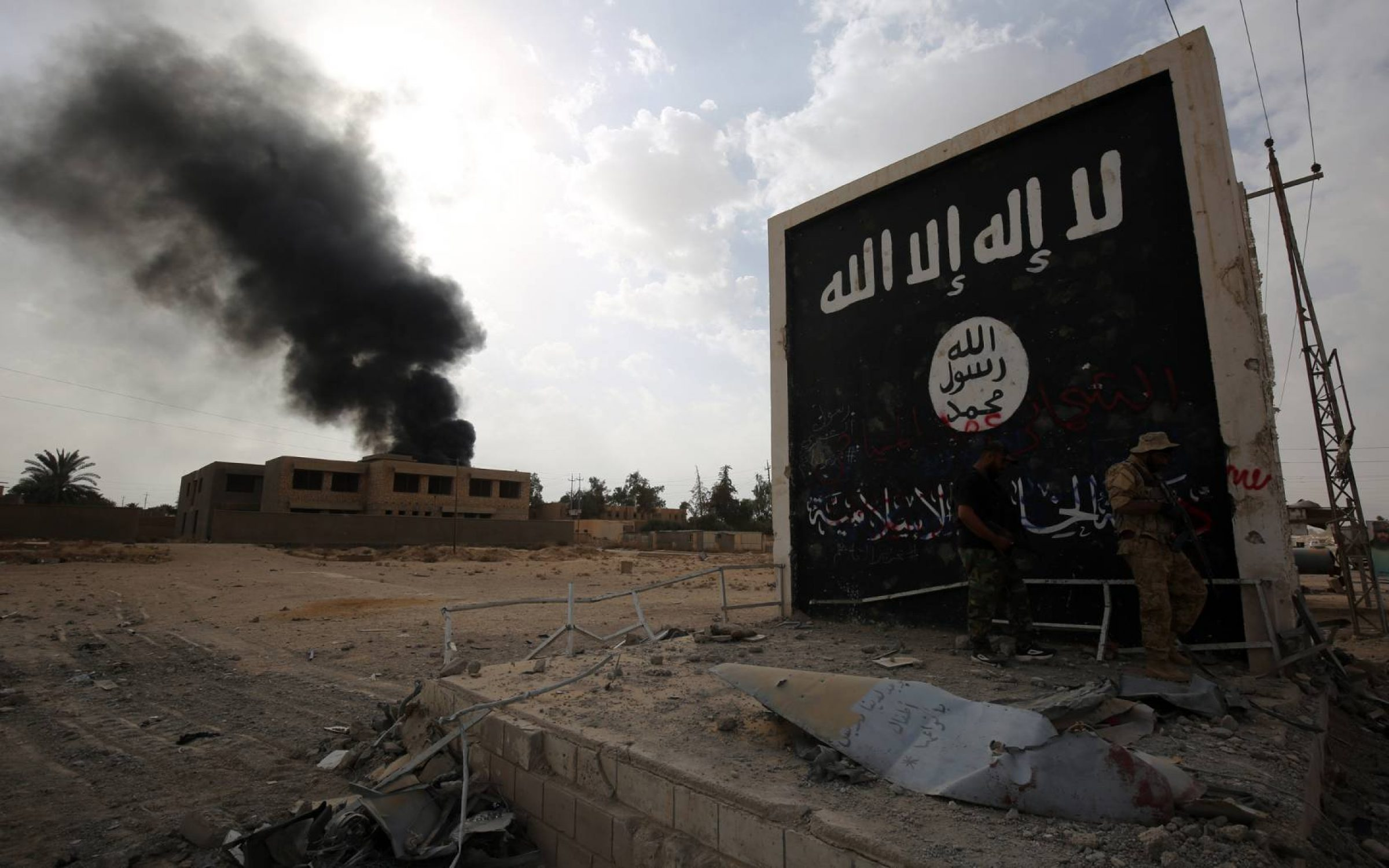 Iraqi fighters of the Hashed al-Shaabi (Popular Mobilisation units) stand next to a wall bearing the Islamic State (IS) group flag as they enter the city of al-Qaim, in Iraq's western Anbar province.