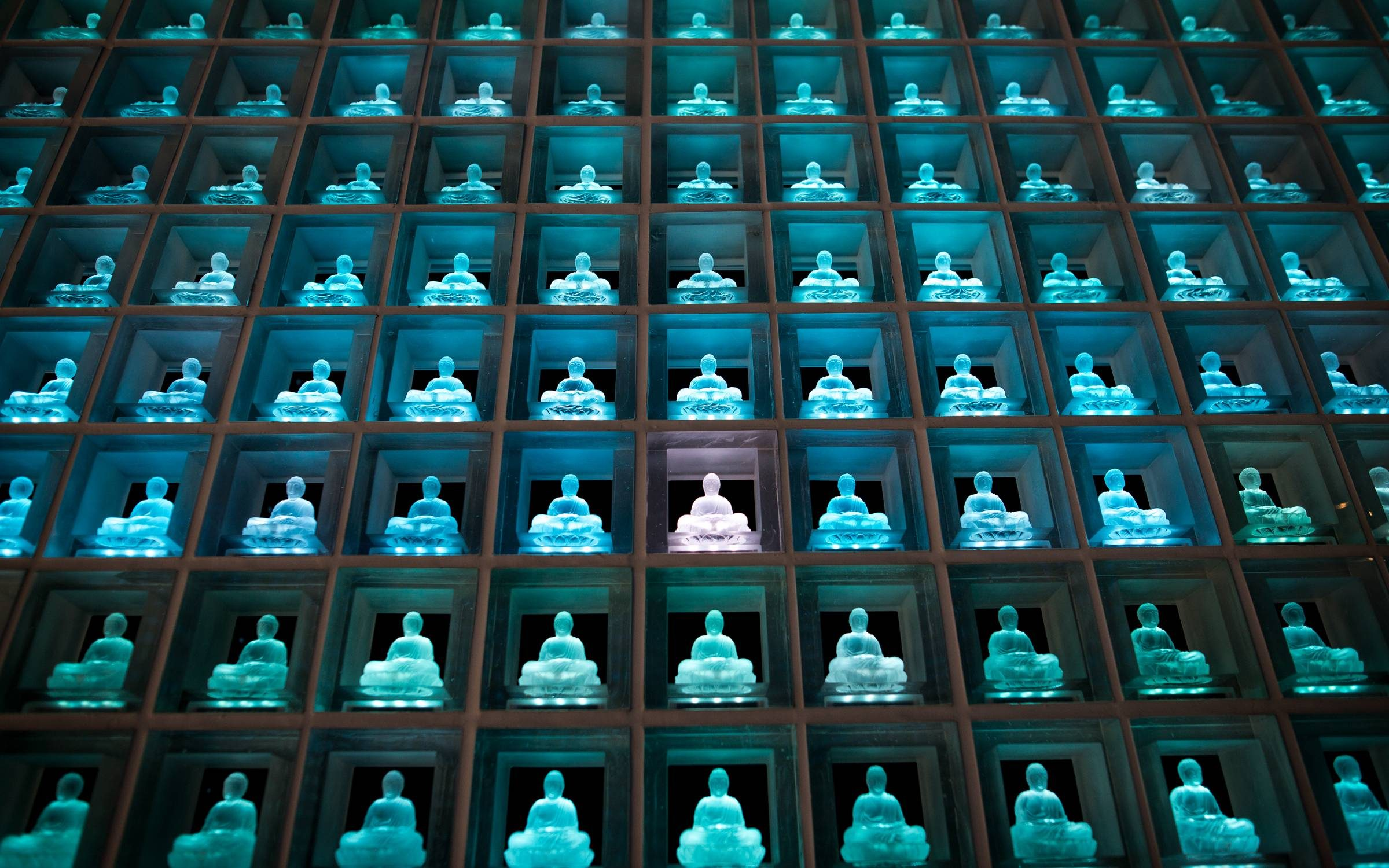Glass Buddha alters are lit up in Koukokuji temple on July 7, 2016 in Tokyo, Japan. Operated by the Koukokuji buddhist temple, The Ruriden columbarium at the Koukoko-ji Temple houses over 2,046 crystal Buddha statues, each illuminated by high-powered LED lights. Behind each Buddha is a drawer storing people's ashes. An IC card allows the owner of the alter to access the building and lights up the corresponding statue. The ashes are stored for 33 years before being buried below the Ruriden, currently 900 alters are in use as of July 2016. (Photo by Richard Atrero de Guzman/NurPhoto via Getty Images)
