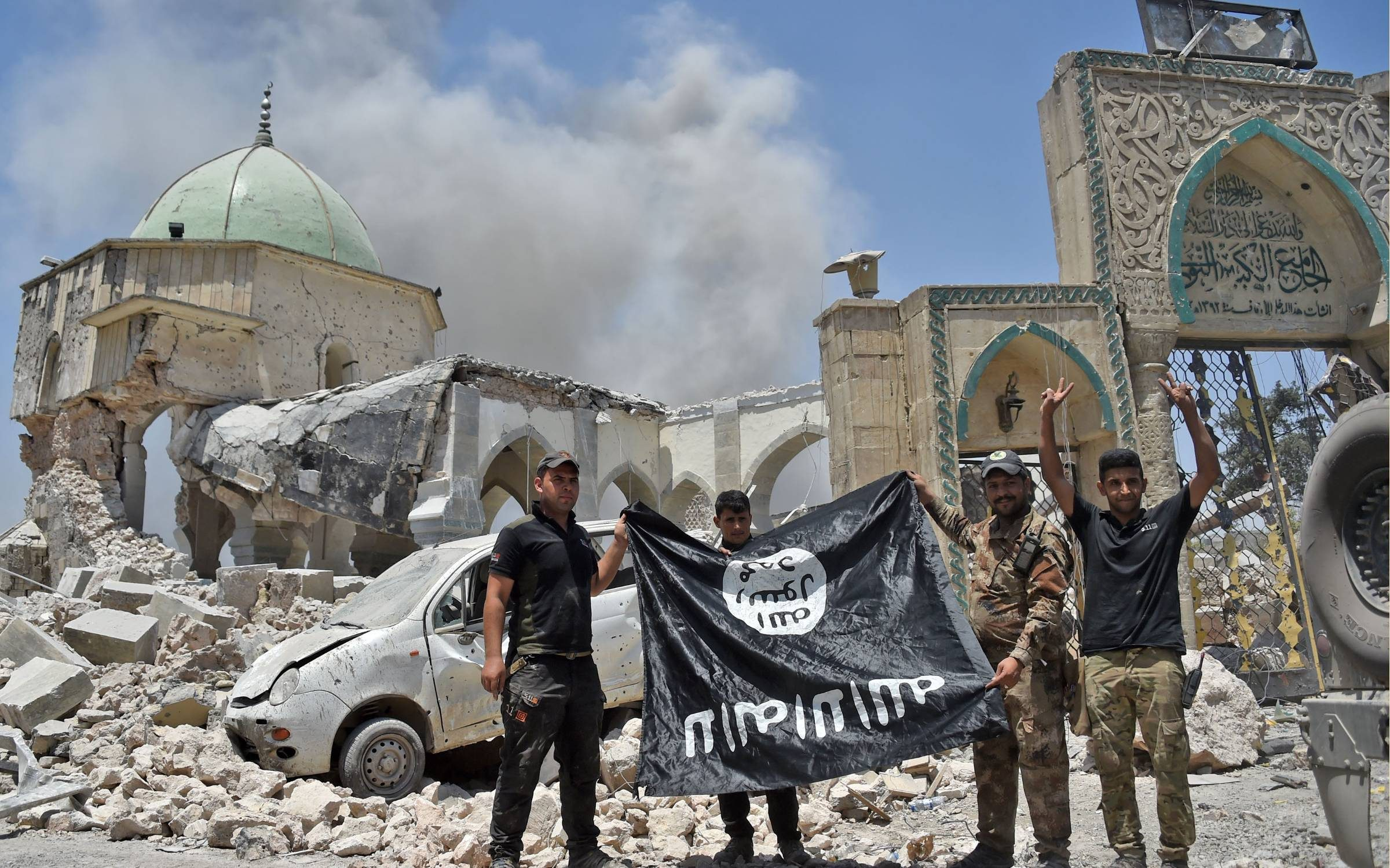 TOPSHOT - A member of the Iraqi Counter-Terrorism Service (CTS) raises the victory gesture as others hold upside-down the black flag of the Islamic State (IS) group, outside the destroyed Al-Nuri Mosque in the Old City of Mosul, after the area was retaken from IS, on June 30, 2017. Explosions on June 21 evening levelled the mosque, where Abu Bakr al-Baghdadi gave his first sermon as leader of the Islamic State group and its ancient minaret. Iraq will declare victory in the eight-month battle to retake second city Mosul from jihadists in the