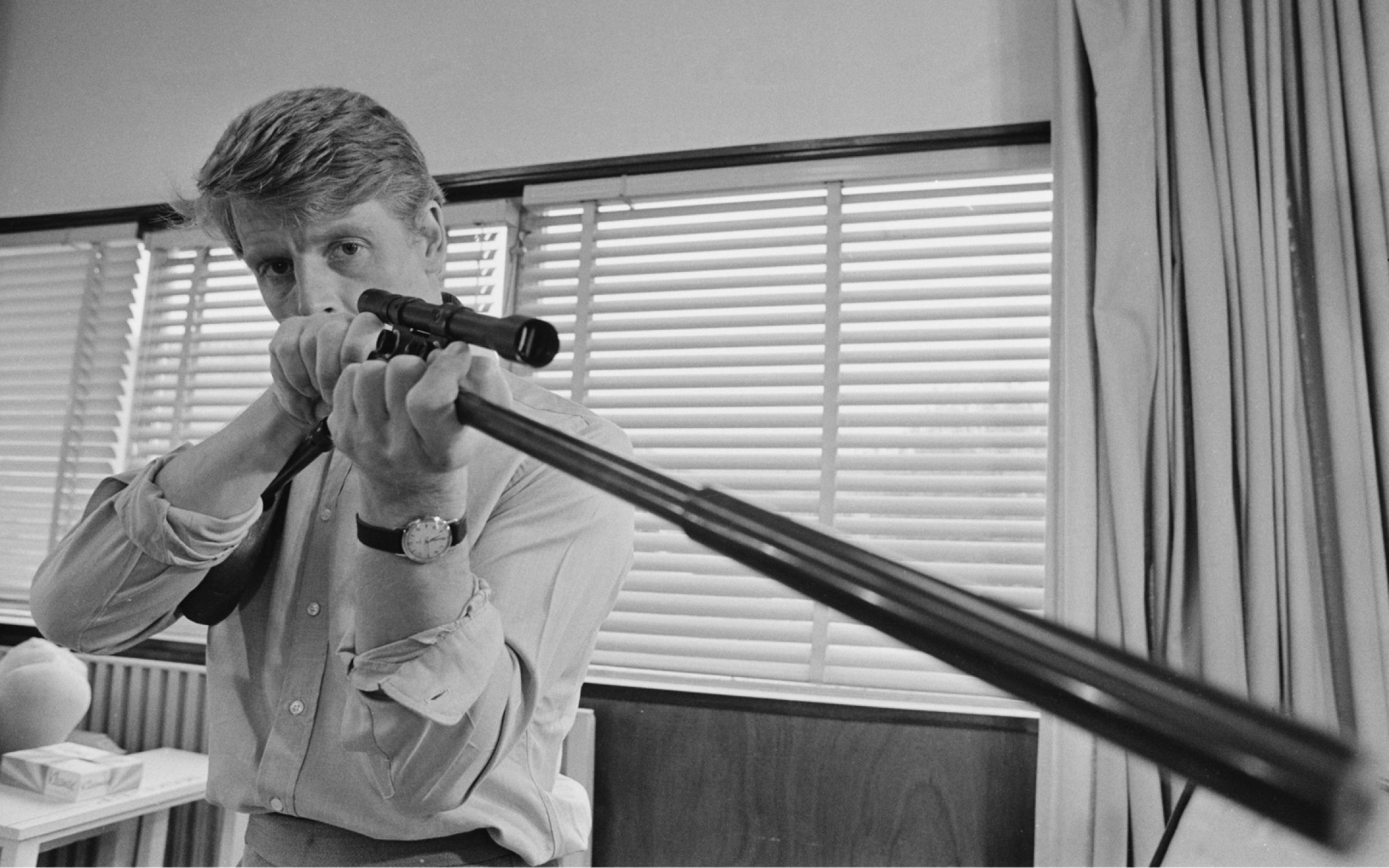 British actor Edward Fox looking through the sight as he aims a rifle during filming of 'The Day of the Jackal',