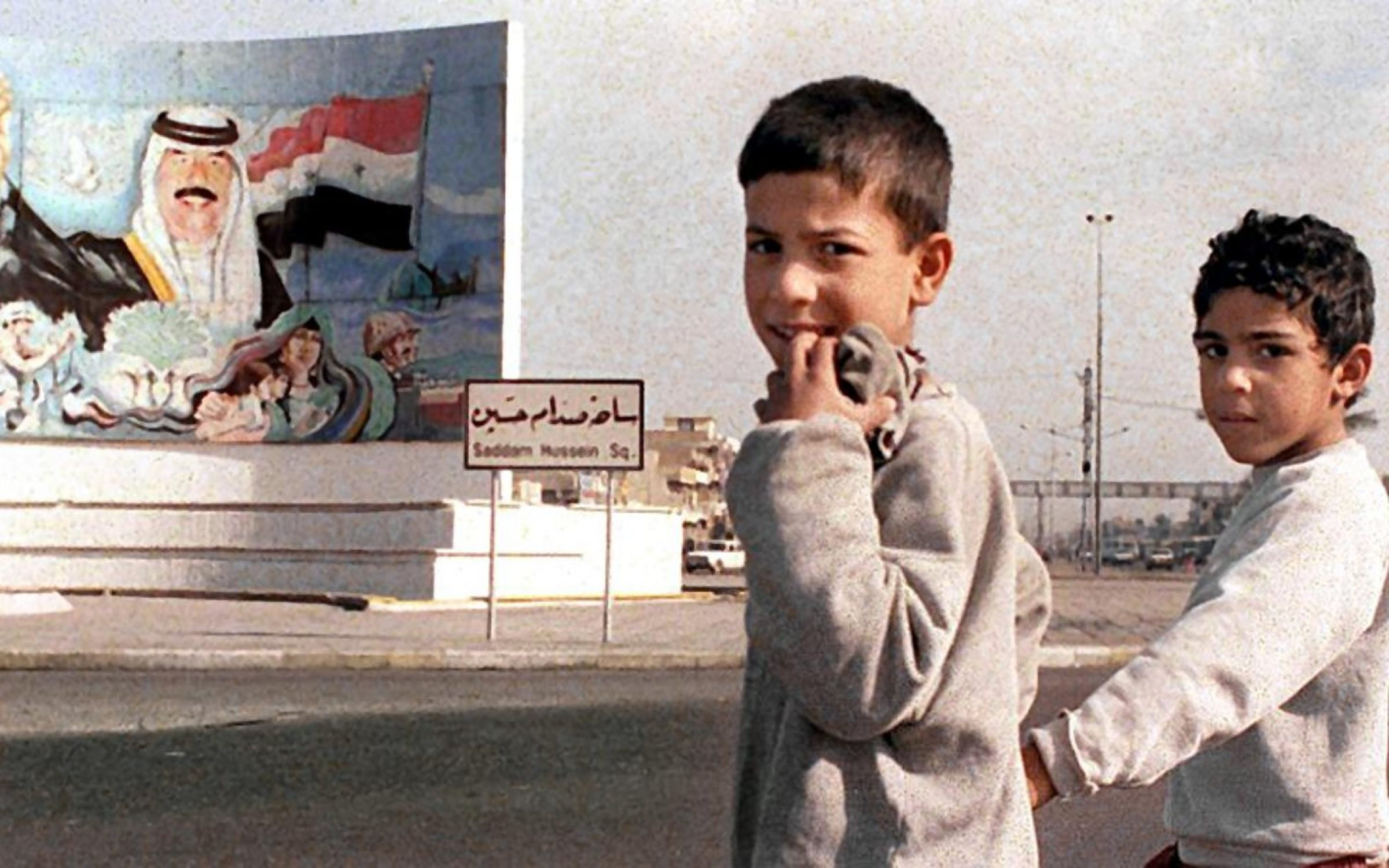 Iraqi children in front of a mural of Saddam Hussein, Baghdad, 1999. Credit: KARIM SAHIB/AFP via Getty Images.