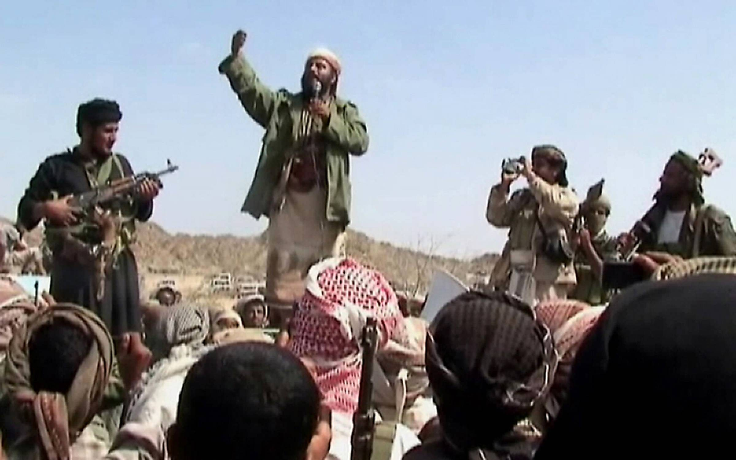 A man claiming to be an Al-Qaeda member addresses a crowd gathered in Yemen's southern province of Abyan on December 22, 2009. Men claiming to be Al-Qaeda members have vowed to avenge those killed in a Yemeni air strike on one of the group's training camps in southern Yemen, Al-Jazeera television reported. In a short video aired by the pan-Arab satellite channel, a bearded man holding a microphone and flanked by two armed men addressed a crowd gathered in the Abyan province to mourn those killed in the December 17 air raid. AFP PHOTO/STR == BEST QUALITY AVAILABLE == (Photo credit should read -/AFP via Getty Images)