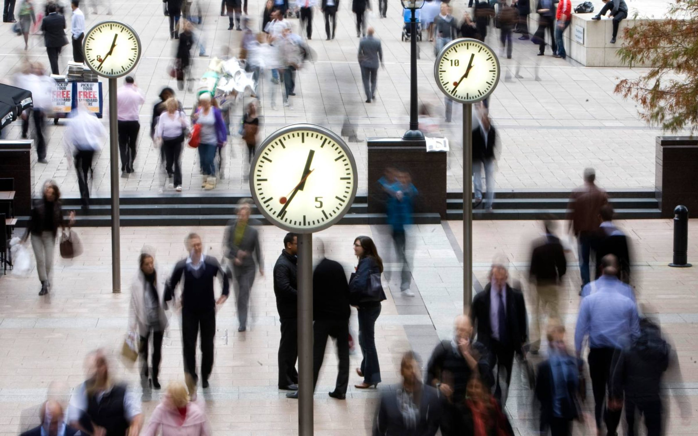 Pedestrians walk past clocks in the financial district of Canary Wharf, London.