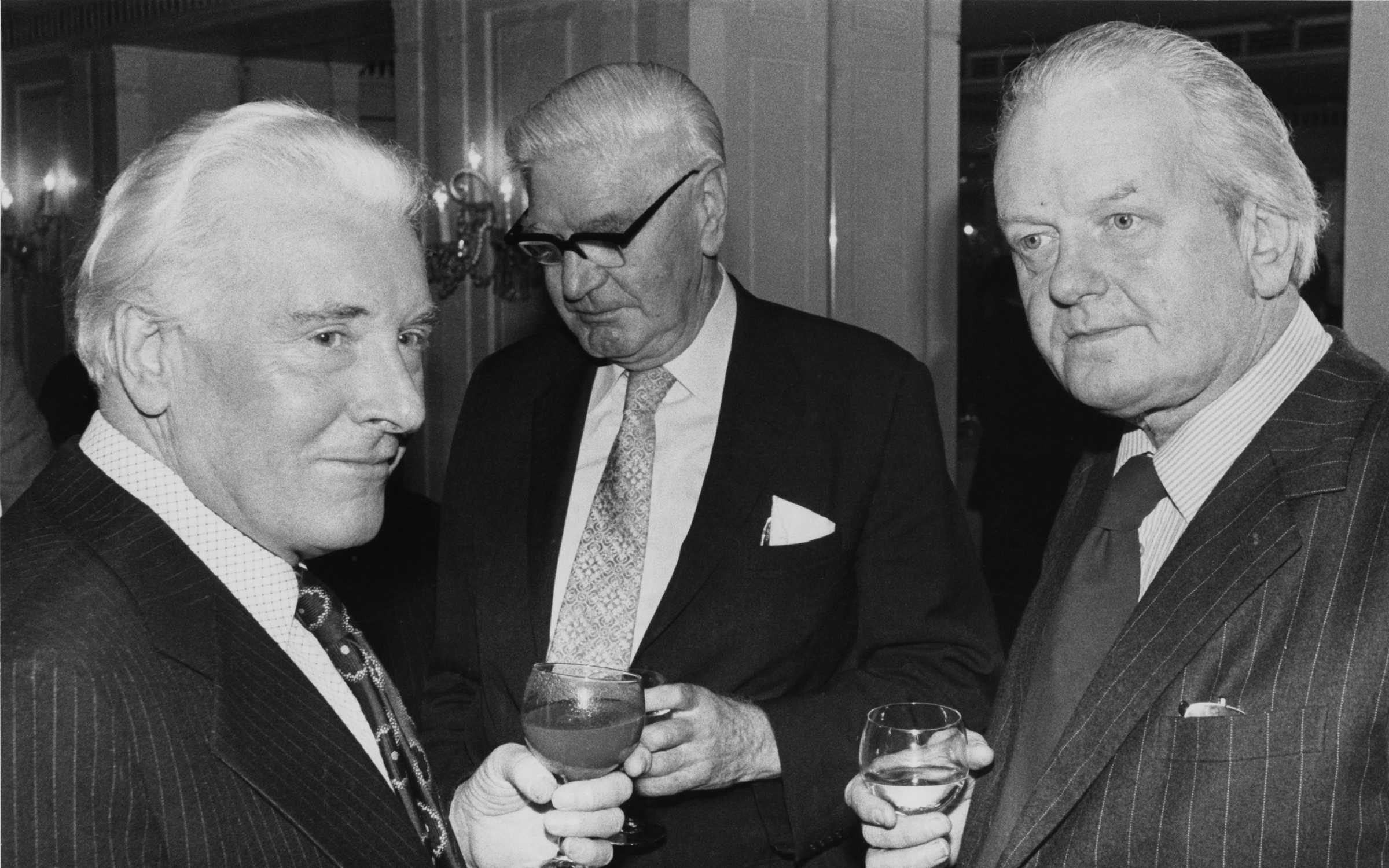 George Kennedy Young (middle) stands between fellow espionage writers Andrew Boyle (left) and Major Douglas Sutherland (right). Credit: Central Press/Hulton Archive/Getty Images.
