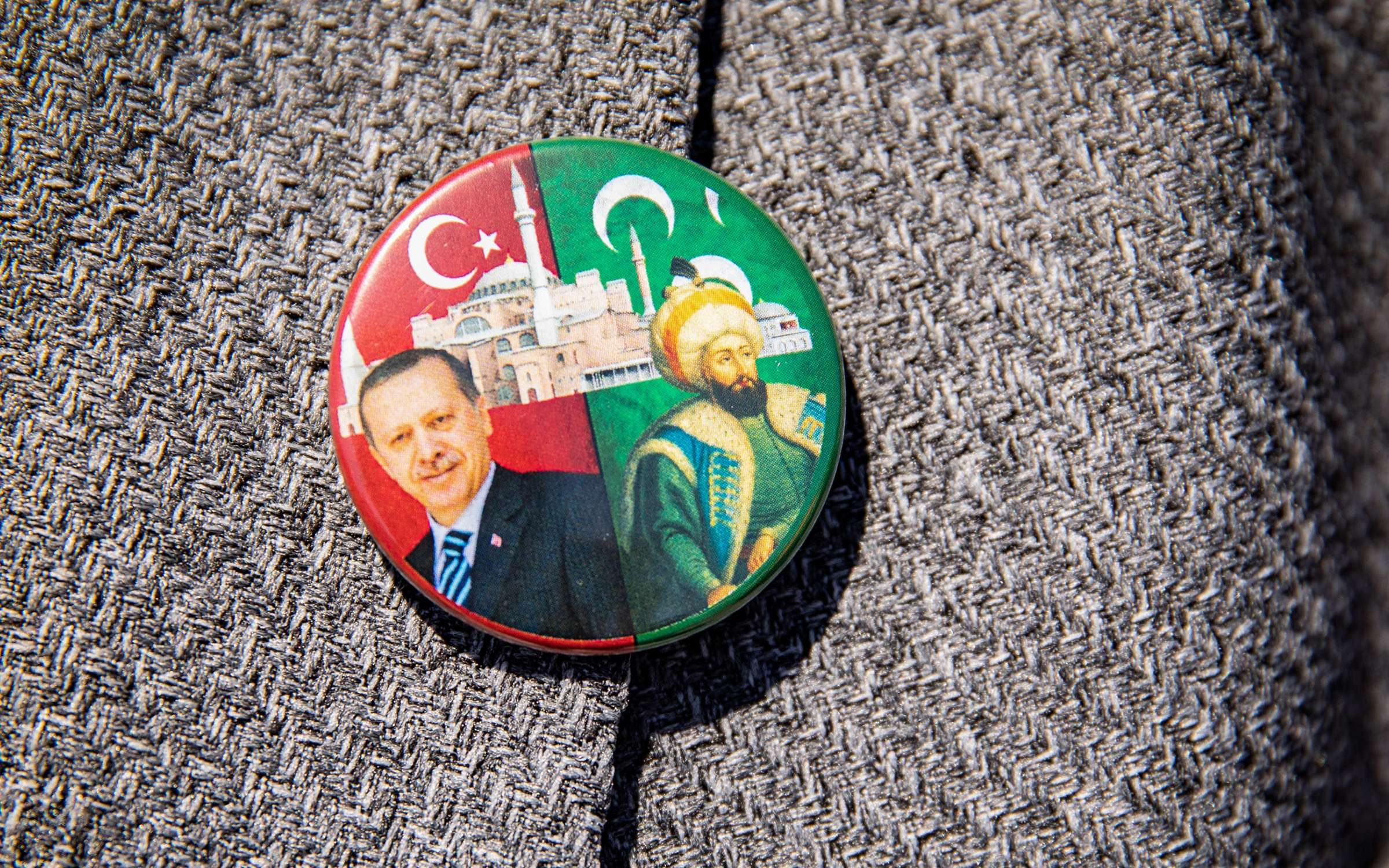 An attendee wears a badge depicting Recep Tayyip Erdogan, Turkey's president, left, during the opening ceremony to mark the first day of prayers at the Hagia Sophia mosque, in the Sultanahmet district of Istanbul, Turkey, on Friday, July 24, 2020. Turkey's President Recep Tayyip Erdogan is holding the first Islamic prayer at the iconic Hagia Sophia in nearly a century, a calculated move to boost the embattled Turkish presidents popularity at home and in the Muslim world. Photographer: Kerem Uzel/Bloomberg via Getty Images