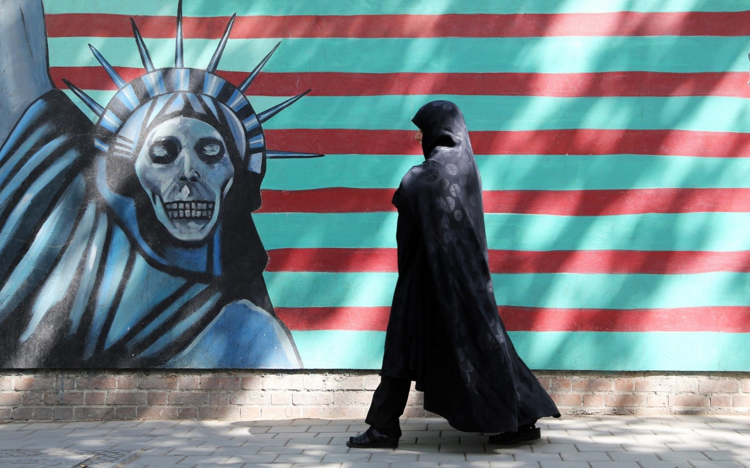 An Iranian woman walks past an anti-US mural depicting the Statue of Liberty on the wall of the former American embassy in Tehran.