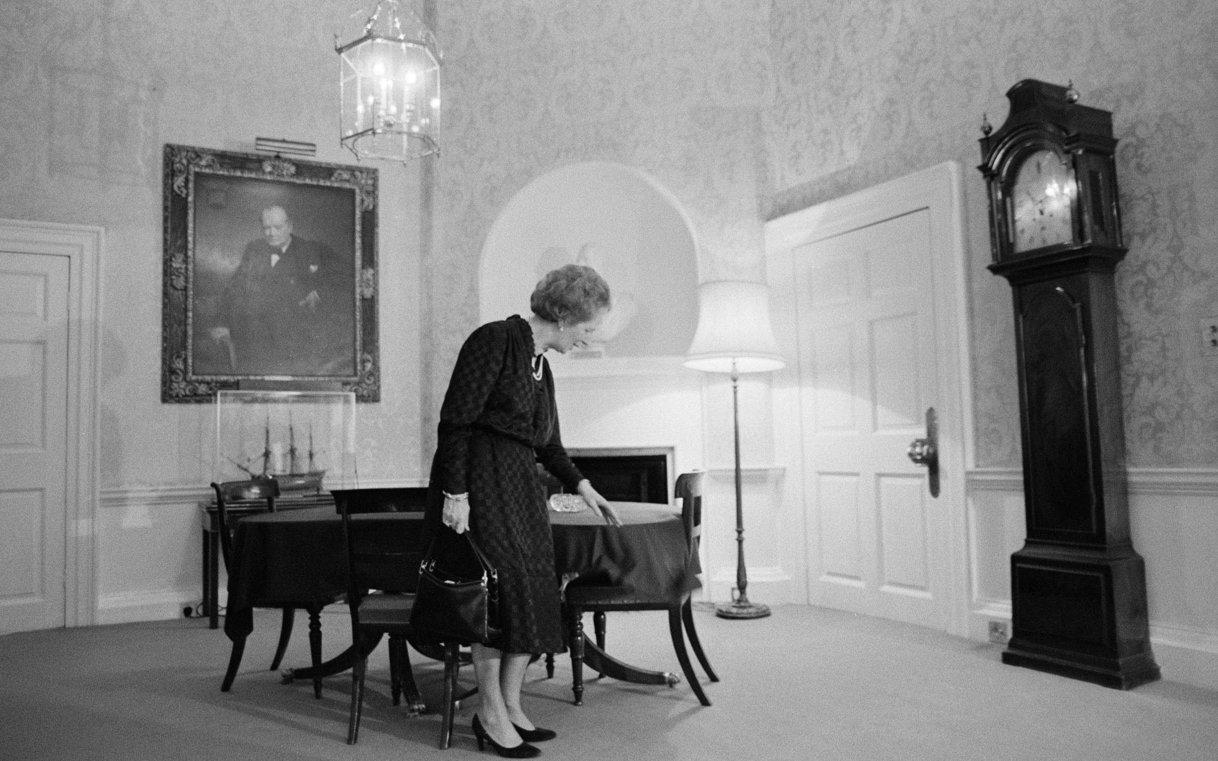 British Conservative prime minister Margaret Thatcher wipes crumbs off the table at 10, Downing Street, London, circa 1990. A painting of her predecessor Winston Churchill hangs on the wall behind her. (Photo by John Downing/Getty Images).